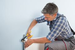 Plumber fixing radiator with wrench Royalty Free Stock Photo