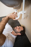 Plumber fixing the sink in a bathroom Stock Image