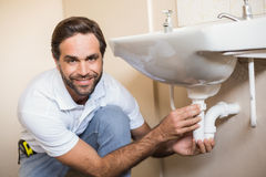 Plumber fixing the sink in a bathroom Royalty Free Stock Photo