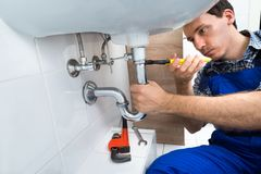 Plumber fixing sink in bathroom Stock Photography
