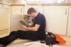 Plumber fixing sink in kitchen consulting tablet computer Stock Photography