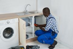 Plumber Fixing Sink In Kitchen. Young African Male Plumber Fixing Sink With Worktool In Kitchen Stock Photography