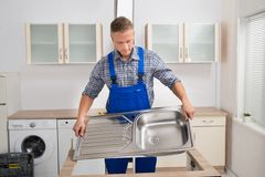 Plumber Fixing Sink. Male Plumber Fixing Stainless Steel Sink In Kitchen Royalty Free Stock Photo
