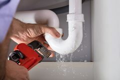 Plumber Fixing Sink Pipe With Adjustable Wrench royalty free stock photography
