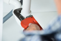 Plumber Fixing Sink Pipe In Kitchen Royalty Free Stock Image