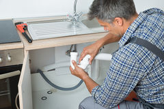 Plumber Fixing Sink Pipe In Kitchen Stock Photo