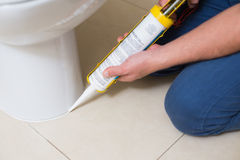 Plumber fixing toilet in a washroom with silicone cartridge. Close up of a plumber fixing toilet in a washroom with silicone cartridge royalty free stock images