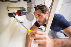 Plumber fixing under the sink Stock Image