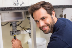 Plumber fixing under the sink Royalty Free Stock Image