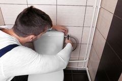 Plumber fixing water hose on cistern. Plumber fixing water hose on toilet cistern stock photos