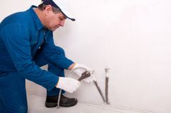 Plumber fixing water pipe Royalty Free Stock Photo