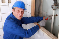 Plumber fixing water supply. In bathroom Stock Image