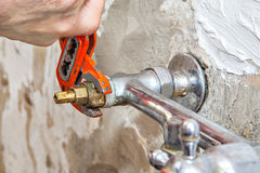 Plumber fixing water tap valve in kitchen, users pliers wrench. Royalty Free Stock Photo