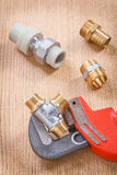 Plumber fixtures and wrench on wooden board Royalty Free Stock Photography
