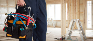 Plumber. Plumber hand with construction tools house renovation background Stock Photo