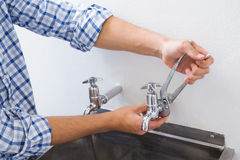 Plumber hand's fixing water tap with pliers royalty free stock photo