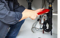 Plumber hand wrench. Professional plumber doing plumbing renovation in kitchen home Stock Image