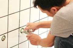 Plumber. Hands fixing water tap with spanner Royalty Free Stock Photography