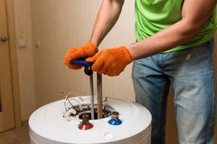 Master put hear element inside water heater. Plumber hands in orange gloves fix boiler indoors royalty free stock photography