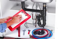 Plumber hands writing on clipboard. Plumbing and renovation royalty free stock photo