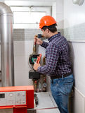 Plumber in hard hat repairing heating system Stock Photos
