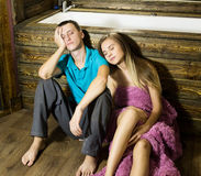 Plumber having flirt with young girl at home. men siting on a floor bathtub, tired and sleepy after flirt with young Stock Images