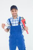 Plumber holding adjustable wrench and sink pipe. Portrait of confident male plumber holding adjustable wrench and sink pipe on white background Royalty Free Stock Images