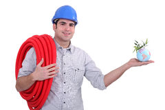 Plumber holding miniature globe Stock Photos