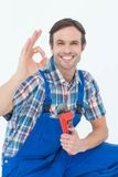 Plumber holding monkey wrench while gesturing OK sign Royalty Free Stock Photography