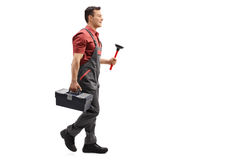 Plumber holding a plunger and a toolbox walking. Full length profile shot of a plumber holding a plunger and a toolbox walking isolated on white background Stock Photos