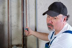 Plumber or homeowner winterising a house. Turning on or off a valve on a water pipe supplying water to the garden Stock Image