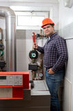 Plumber installing heating system at boiler room Stock Photos