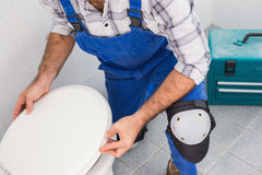 Plumber installing lid on toilet Stock Photography
