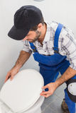 Plumber installing lid on toilet Royalty Free Stock Images
