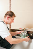Plumber installing a mixer tap in a bathroom Stock Images