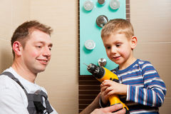 Plumber installing a mixer tap in a bathroom. He explains it to his son stock images