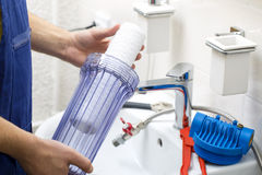 Plumber installing new water filtration system Stock Image