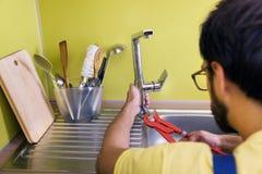 Plumber installing, repairing water tap in kitchen Royalty Free Stock Images