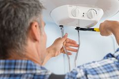 Plumber installing water heater Stock Images