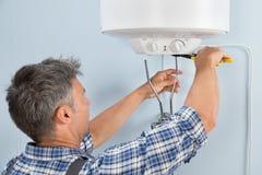 Plumber installing water heater Stock Image