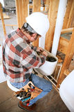 Plumber Installs Toilet. Plumber installing a toilet on a construction site royalty free stock photos