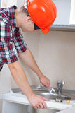 Plumber installs water tap Stock Photos