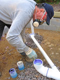 Plumber joining plastic pipes. With cement for drains lines that will be under a concrete slab Stock Image