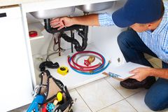 Plumber on the kitchen. Stock Photos