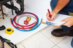 Plumber on the kitchen. Royalty Free Stock Images
