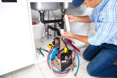 Plumber on the kitchen. Plumber with Plumbing tools on the kitchen. Renovation royalty free stock photos