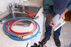 Plumber on the kitchen. Plumber with Plumbing tools on the kitchen. Renovation stock photos