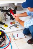 Plumber on the kitchen. Royalty Free Stock Photography