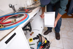 Plumber on the kitchen. Plumber with Plumbing tools on the kitchen. Renovation royalty free stock images