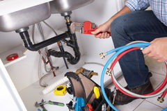 Plumber on the kitchen. Plumber with Plumbing tools on the kitchen. Renovation stock photography